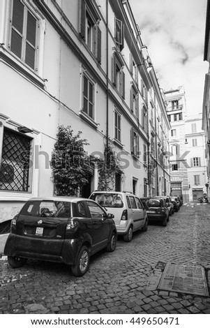 Rome, Italy - February 13, 2016: Ordinary street in old Rome with cars parked on a roadside, black and white