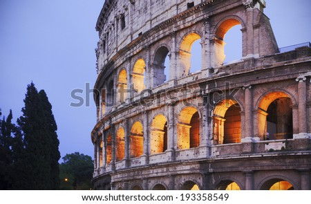 Rome, Italy. Illuminated Coliseum at dusk with copy space on left - stock photo