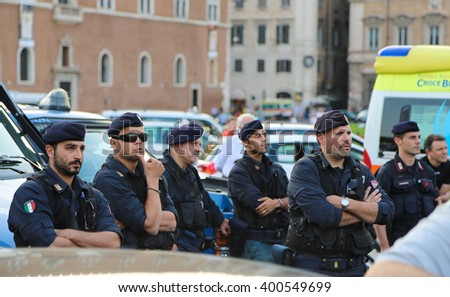 Rome, Italy - June 25, 2014: A group of armed police officers standing near the police car on one of the main streets of Rome during a public event. Police are closely monitoring what is happening. - stock photo