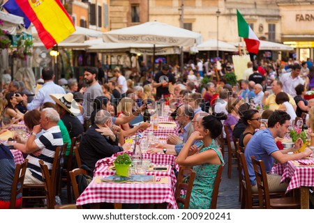ROME, ITALY - JUNE 13 2014: People having aperitif which in Italy traditionally includes free all you can eat buffet of pizzas and pastas, on JUNE 13 2014 on Piazza Campo De Fiori in Rome in Italy. - stock photo