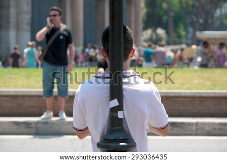 Rome, Italy - June 26, 2010: unidentified guy lean to streetlamp, unidentified man talking phone, tourists around Colosseo District