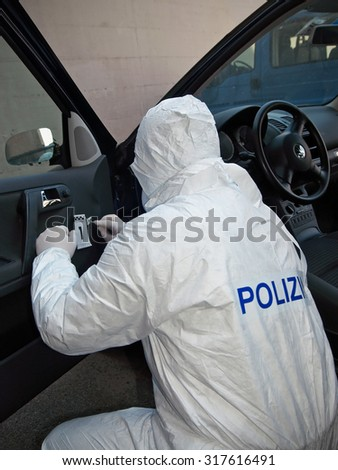 Rome, Italy - March 29, 2004: A police officer scientific finds of traces in a car seized. - stock photo