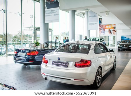 ROME, ITALY - MARCH 10, 2014: Agents selling BMW cars inside car dealer showroom. The BMW Group recorded increasing of sales in Italy.