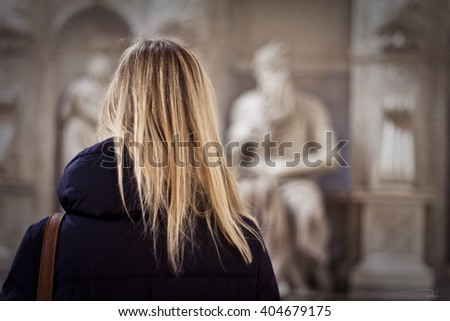 ROME, ITALY - MARCH 10, 2012: Tourist woman standing in front of the statue of Moses sculpted by Michelangelo in the San Pietro in Vincoli church. Selective focus. - stock photo