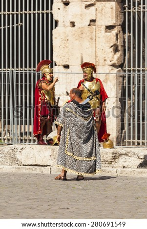 ROME, ITALY - MAY 22, 2014: Actors playing a Roman legionary for tourists near the Colosseum. Rome, Italy - stock photo