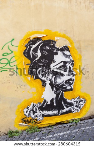 ROME, ITALY - MAY 21, 2014 - Graffiti by street artist on a building one of the back streets of Rome, these art doesn't match well with the city culture - by critic. - stock photo
