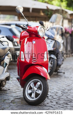 Rome, Italy - May 27, 2016: Old red Vespa parked on old street in Rome, Italy. - stock photo