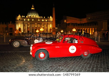 ROME ITALY - MAY 17: Red Fiat 508, built in 1938, and brown Alfa Romeo 6C, 1940, drive by Piazza San Pietro during 1000 Miglia historic car race, on May 17, 2013 in Rome - stock photo