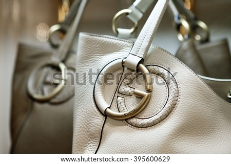 "ROME, ITALY - 19 NOVEMBER 2012: A pair of Gucci 'Twill' bags bearing the interlocking ""G"" logo sit displayed for sale inside a Gucci store."