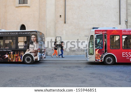 ROME, ITALY - OCTOBER 4: Two painted buses in the street of Rome city on October 04, 2011. Rome's Public Transport system includes metro, buses and trams.