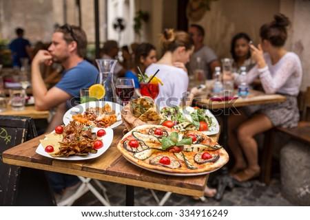 Rome, Italy - September 11, 2015: Unidentified people eating traditional italian food in outdoor restaurant in Trastevere district in Rome, Italy. - stock photo
