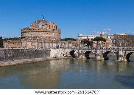ROME, ITALY - 12TH MARCH 2015: Castel Sant'Angelo (Castle of the Holy Angel) and part of the Ponte Sant'Angelo bridge from the side. People can be seen around the building and on the bridge - stock photo