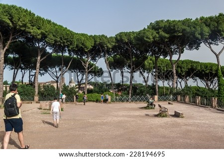 ROME - JUNE 24, 2014: Tourists visiting park at the ruins of Rome Forum on June 24, 2014 in Rome. The park is situated at the top of some ancient structures, - stock photo