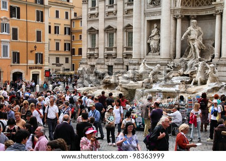 ROME - MAY 11: Tourists watching Trevi Fountain on May 11, 2010 in Rome, Italy. Trevi Fountain is among most iconic fountains in the world and one of Italy's top tourism destinations. - stock photo