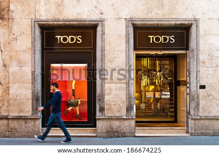 ROME - SEPTEMBER 18: unidentified man walking past Tod's at Via dei Condotti in Rome, Italy on September 18, 2013. Italian brand produces luxury shoes and leather goods with stores around the world. - stock photo