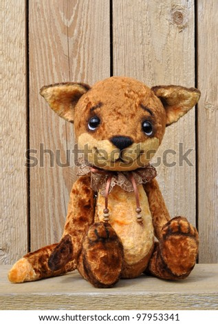 Ron fox cub on the background of a wooden plank wall. Handmade, the sewed plush toy - stock photo