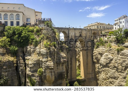 Ronda Panoramic view over Puente Nuevo, New Bridge. The newest of three bridges that span the 120-metre deep chasm that carries the Guadalev�­n River and divides the city of Ronda, in southern Spain. - stock photo