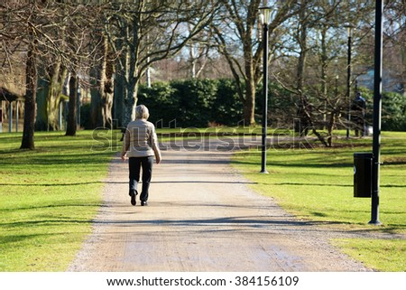 Ronneby, Sweden - February 26, 2016: An unknown woman seen from behind as she walks on a walkway in the park Ronneby Brunn. It is early spring and the weather is fine but cold.