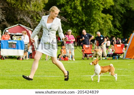 RONNEBY, SWEDEN - JULY 05, 2014: Blekinge Kennelklubb international dog show. Adult female handler with Basenji dog in ring. - stock photo