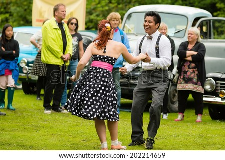 RONNEBY, SWEDEN - JUNE 28, 2014: Nostalgia Festival, classic cars, motorcycles, fashion and entertainment. Dancers dressed in old times clothing performing at carshow. - stock photo