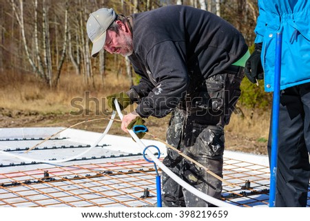 Ronneby, Sweden - March 26, 2016: Carpenter measuring some plastic tubing for floor heating with a wooden ruler on a construction site. Real people in everyday life.