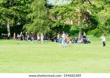 RONNEBY, SWEDEN - MAY 24, 2014: Group of people relaxing and having fun in public park. Green grass and ball play. - stock photo