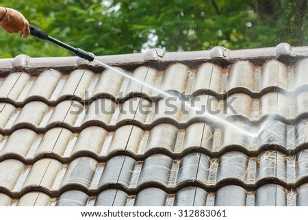 Roof cleaning with high pressure water cleaner - stock photo