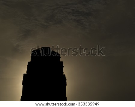 Roof comb of a Tikal mayan temple in silhouette - stock photo