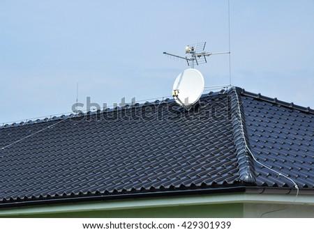Roof covering TV satellite antenna - stock photo
