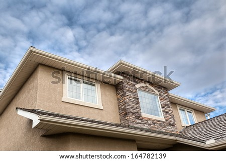 Roof line showing windows, brick stones, gutter, soffit, stucco - stock photo