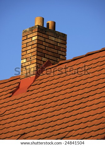 Roof made of terracotta rooftiles with brick chimney - stock photo