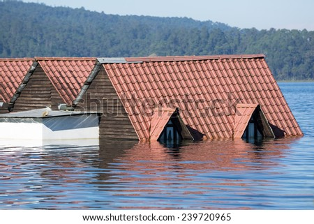 roof of a house in flood water  - stock photo