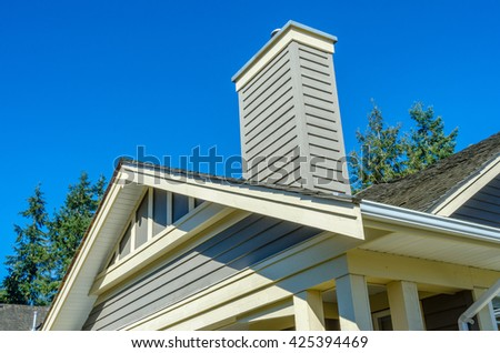 Roof of a modern house with chimney pipe in great neighborhood in suburbs of Vancouver.