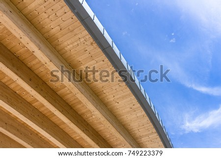 Roof of an ecologically clean wooden house against a beautiful cloudy blue sky. Bottom view. Space for text.