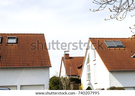 Roof of classic residential houses with orange roofing tiles and windows