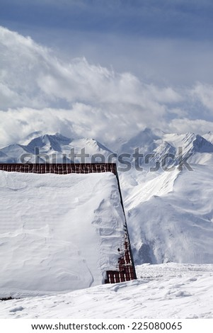 Roof of hotel in snow and ski slope. Caucasus Mountains, Georgia, ski resort Gudauri. - stock photo