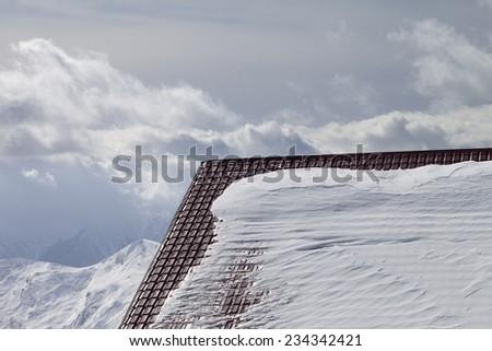 Roof of hotel in snow and winter mountains. Caucasus Mountains, Georgia, ski resort Gudauri. - stock photo