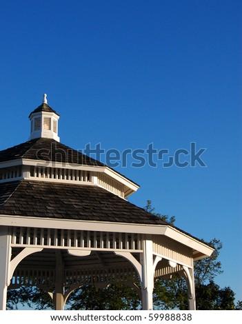 Roof of ornate gazebo with blue sky background - stock photo