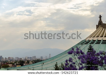 Roof of the Basilica of our Lady of Guadalupe with Mexico City skyscrapers in the background - stock photo