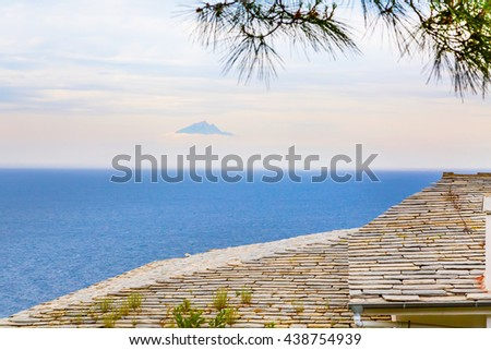 Roof of the old monastery house, seascape and mount Athos far away in the clouds, Greece - stock photo
