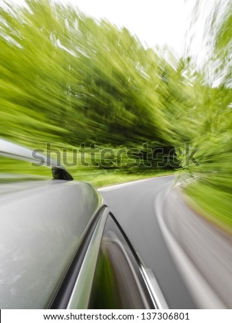 Roof rack view of a caravan car driving fast on a winding road in the woods - stock photo