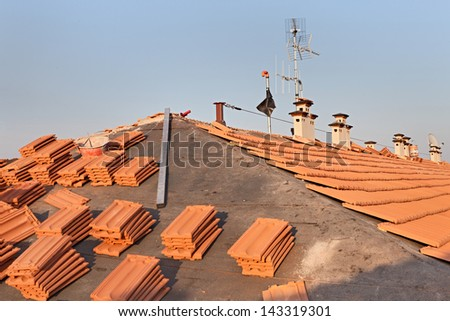 roof renovation: installation of tar paper, new tiles, chimney and tv antenna - stock photo