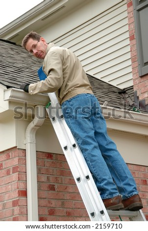 Roof Repair - Man on a ladder, cleaning the gutters and repairing the roof shingles. - stock photo