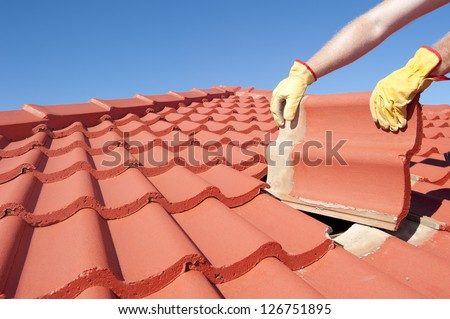 Roof repair, worker with yellow gloves replacing red tiles or shingles on house with blue sky as background and copy space. - stock photo