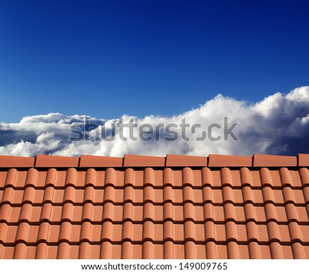 Roof tiles and sunny sky with clouds - stock photo