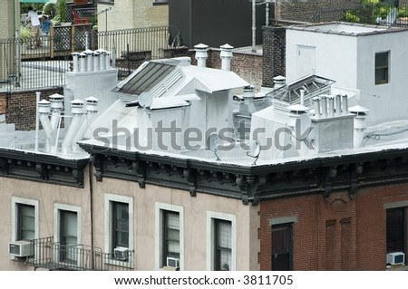 Roof top of an apartment building in New York City with exhaust ducts, vent pipes and satellite dishes. - stock photo