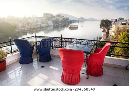 Roof top restaurant with beautiful view to Lake Pichola in the morning in Udaipur, Rajasthan, India - stock photo
