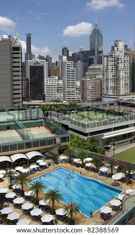 Roof top sport complex with swimming pool and tennis courts in downtown Hong Kong - stock photo