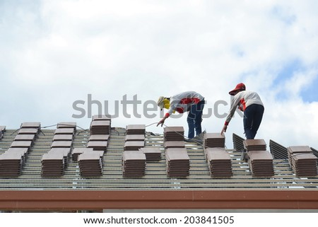 roof under construction with stacks of roof tiles - stock photo