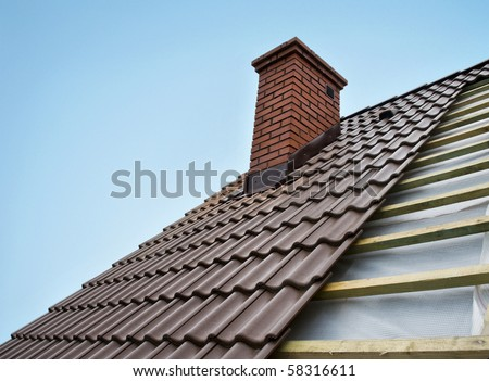 Roof under constructions with lots of tile and red brick chimney - stock photo